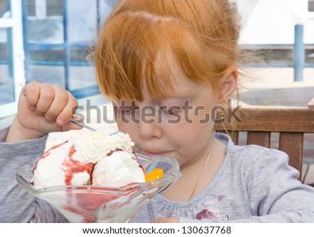A little girl eating ice cream - stock photo