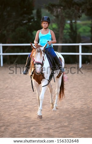 A little girl getting a horseback riding lesson