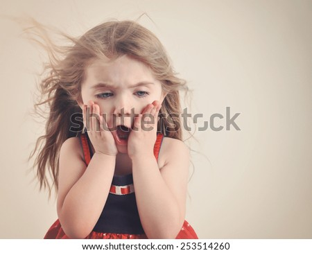 A little girl has an open mouth with hair blowing on a retro background for a surprise or shock concept. - stock photo