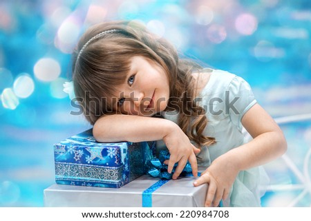A little girl holding christmas gift on the blue background - stock photo