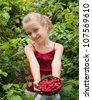 a little girl holding raspberries - stock photo