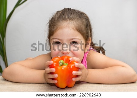 A little girl holds a pepper with both hands to her mouth - stock photo