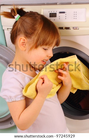 A little girl holds a towel after washing - stock photo