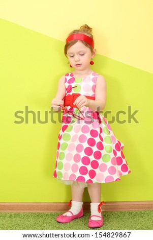 A little girl in a bright varicolored dress holding a rim of glasses