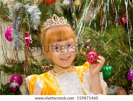 A little girl in a dress of Princess around the Christmas tree  - stock photo