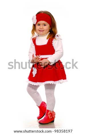 a little girl in a knitted dress on a white background