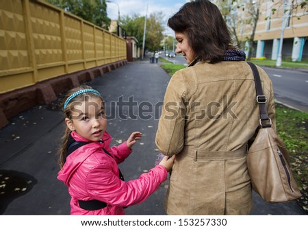 A little girl in a pink jacket walking in the street with her ??mother. Real people series.