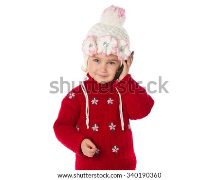 A little girl in a red sweater talking on the phone isolated on a white background. - stock photo