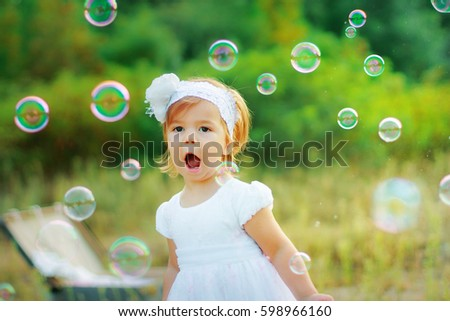 A little girl in a white dress and with a flower on her head is happy with soap bubbles. The child catches soap bubbles. Baby walking in the park