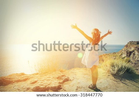 A little girl in a white dress standing on the edge of a mountain and looking at sea - stock photo