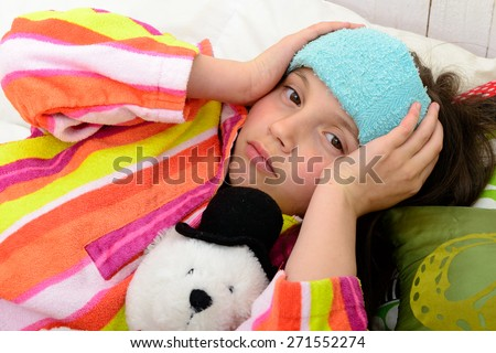 a little girl in her bed has a headache - stock photo