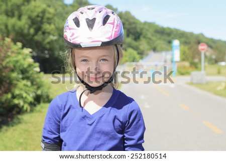 A Little girl in roller skates at a park - stock photo