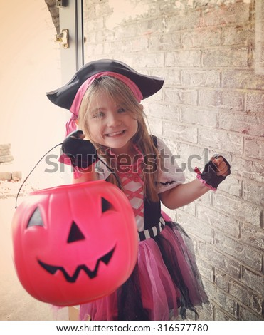 A little girl is dressed up in a pink pirate costume trick or treating at a door with a pumpkin basket and smiling. - stock photo