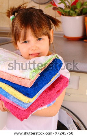 A little girl is going to wash the towels - stock photo