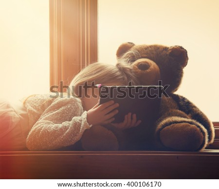 A little girl is holding a technology tablet in a sunny window at home with a teddy bear toy for an entertainment or leisure concept. - stock photo