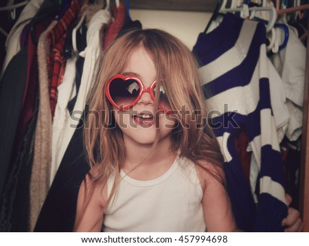 A little girl is in a closet of messy clothes with red glasses for a style or fashion concept. - stock photo