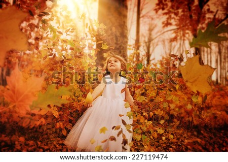 A little girl is in the woods with trees and fall leaves blowing in the wind around her. The child is wearing a white pretty dress for a season or happiness concept. - stock photo