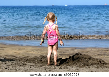A little girl is looking at the ocean and the horizon
