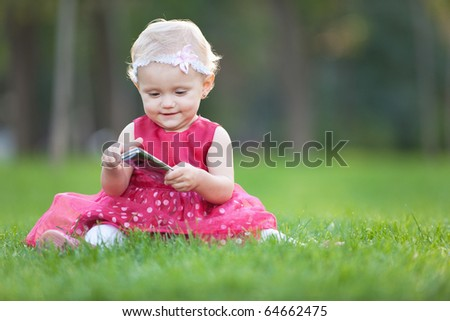 A little girl is playing with a mobile on the grass