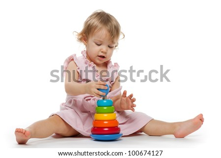 A little girl is playing with toy; on the white background