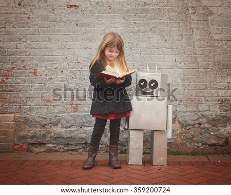A little girl is reading a book with a metal cardboard robot next to her against a brick wall for an education or creativity concept - stock photo