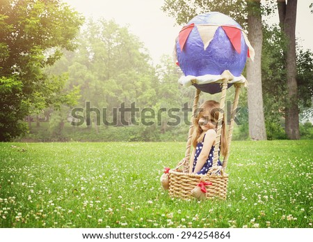 A little girl is sitting in a hot air balloon basket in the park pretending to travel and fly with for a creativity or imagination concept. - stock photo