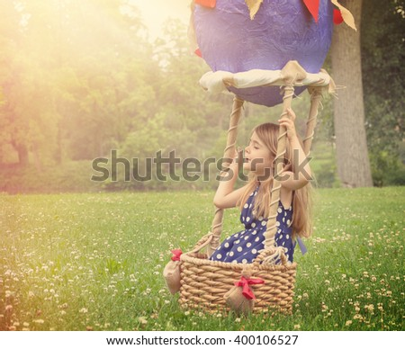 A little girl is sitting in a hot air balloon basket in the park pretending to travel and fly with a sunshine on for a creativity or imagination concept.