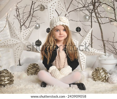 A little girl is sitting in a white winter wonderland setup with trees, hanging stars and Christmas lights in the background for a season or holiday concept.  - stock photo