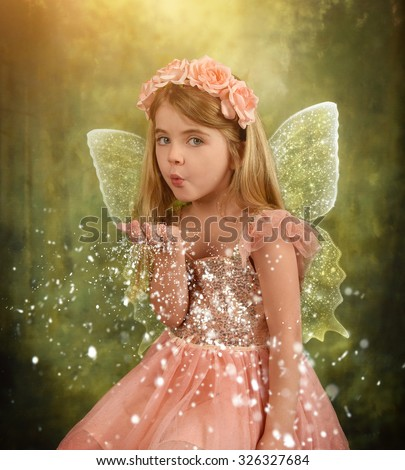 A little girl is sitting in the woods with sparkle fairy wings blowing magical dust for an imagination or fairy tale concept.  - stock photo