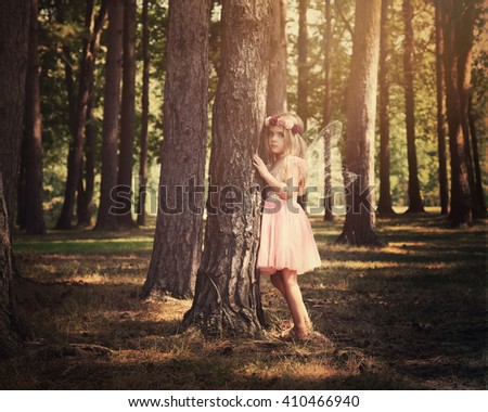 A little girl is standing in the woods with sparkle fairy wings for an imagination or fairy tale concept.  - stock photo