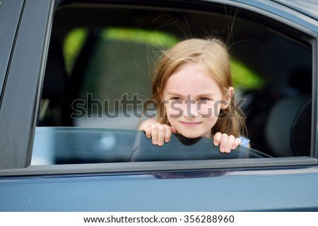 A little girl is sticking her head out the car window looking forward for a roadtrip or travel - stock photo