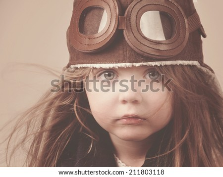 A little girl is wearing a pilot hat with goggles with an antique concept for career or imagination message. - stock photo