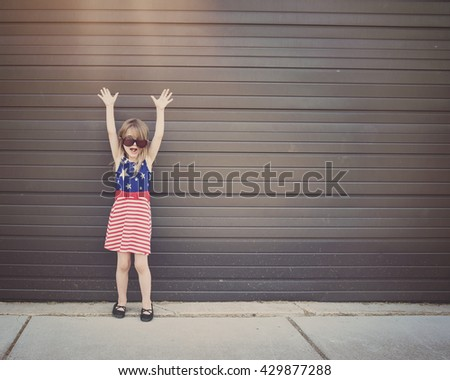 A little girl is wearing glasses standing outside against a wall with her arms up for a freedom, happiness or excitement idea - stock photo