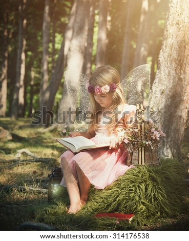 A little girl is wearing white sparkle fairy wings outside in the woods reading a fairy tale book for an education or magical story concept - stock photo
