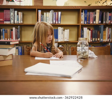 A little girl is writing on paper in a library and looking at a jar of money that says education for a savings or college concept. - stock photo