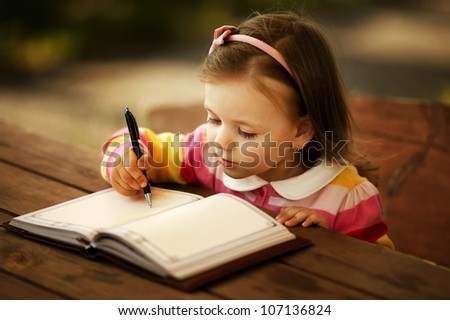 a little girl learning to write - stock photo
