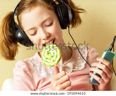 A little girl listening to music with headphones, holding a mobile phone and a Lollipop. - stock photo