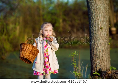 a little girl of 4 years is near the pond with a wicker basket and blowing on a dandelion