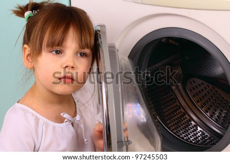 A little girl opens the washing machine - stock photo