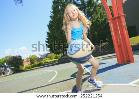 A little girl play basketball with on the playground - stock photo