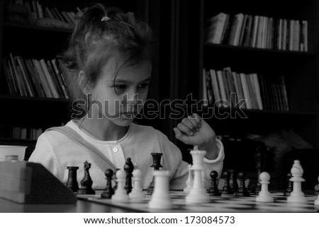 A little girl playing real chess in competition. Black and white photo. Concentrated kid. Power of concentration