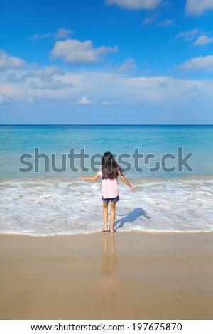 A little girl playing sea wave on nice sand beach - stock photo