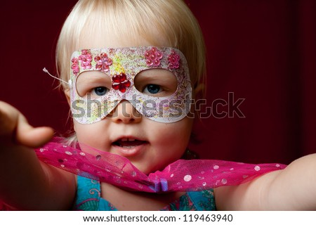 A little girl plays dress-ups as a super hero. - stock photo