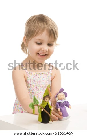 A little girl plays with gnomes on white
