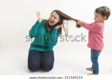 A little girl pulls her older sister hair - stock photo