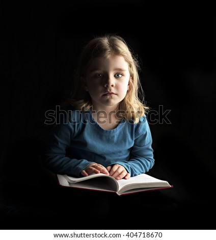 A little girl reading a book - stock photo