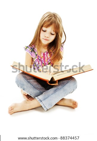 A little girl reading a book on the floor. Isolated on white background - stock photo