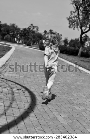 A little girl running along the path of a park, black and white photo - stock photo