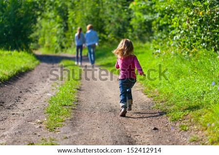 A little girl running down the road for her mother and sister - stock photo