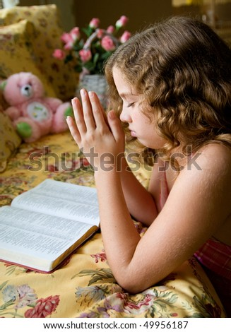 A little girl saying her prayers. - stock photo